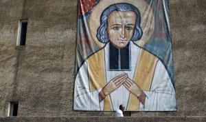 03 juillet 2010: Un moine de la communauté Saint Jean passe devant un portrait géant de St Jean Marie Vianney, Ars-sur-Formans (01), France. July 3th, 2010: A monk walks past a giant portrait of Saint Jean-Marie Vianney, Ars-sur-Formans, France.
