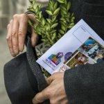 25 mars 2018 : Dimanche des Rameaux. Homme tenant à la main du buis et une enveloppe du Denier de l'Eglise. Bondy (93), France.