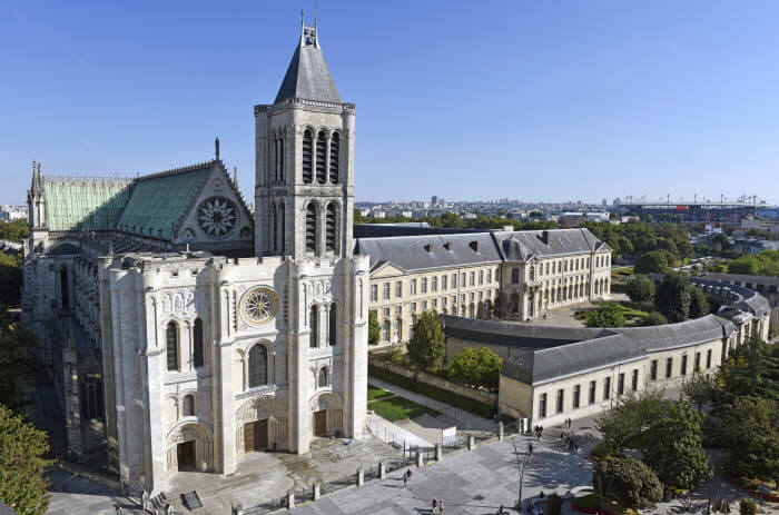 10 Septembre 2015 : La basilique de Saint Denis et sa façade occidentale récemment restaurée (2012/2015), l'école de la Légion d'Honneur, et, au fond, le Grand Stade. Saint-Denis (93), France.  September 18, 2015: The recently restored west facade of St Denis Basilica. Saint-Denis (93) France.
