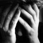 Jeune homme tenant son visage dans ses mains pour illustrer le suicide