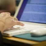 Evêque prenant des notes sur son ordinateur portable