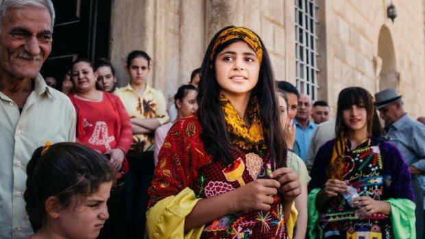 24 juillet 2017 : Paroissiens de Qaraqosh attendant Mgr Philippe BARBARIN, archevêque de Lyon et Mgr Petros MOUCHE, évêque syriaque catholique de Mossoul et Qaraqosh, devant l'église Al-Tahera (Notre-Dame de l'Immaculée Conception) de Qaraqosh, où ils célèbreront une messe. Avant d'être envahie par Daech le 6 août 2014, Qaraqosh comptait plus de 54000 habitants. La ville a été libérée par l'armée irakienne en octobre 2016. En juillet 2017, plus de 400 familles étaient revenues s'installer dans leurs maisons, pour la plupart détruites, incendiées et pillées. Quelques jours avant la prise de Qaraqosh par l'Etat Islamique, Mgr BARBARIN avait initié à Qaraqosh le jumelage des diocèses de Lyon et de Mossoul. Qaraqosh, Irak.