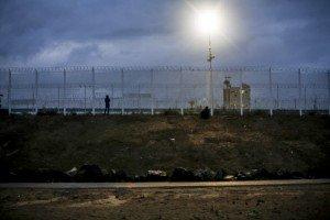 """19 octobre 2016 : Des migrants et réfugiés cherchent du réseau pour leurs téléphones aux abords des clôtures les séparant de l'autoroute. Vue de la """"jungle"""" à quelques jours du démantèlement final du plus grand bidonville d'Europe. Calais (62), France."""