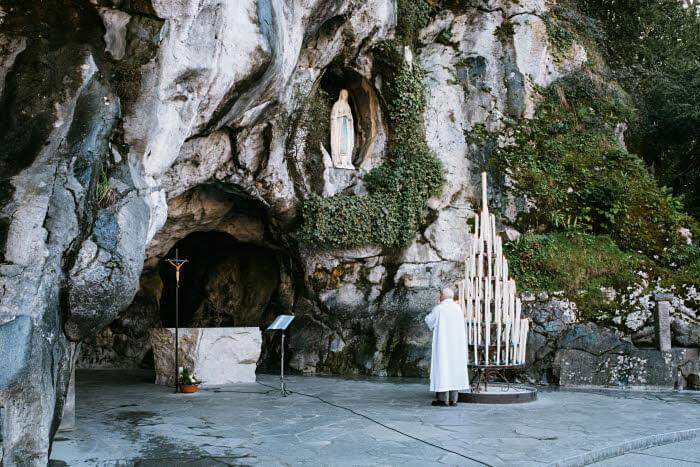 24 janvier 2018 : Un prêtre prie devant la grotte de Massabielle à Lourdes (65), France.