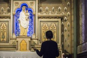 15 mars 2019 : Illustration, femme priant devant une Vierge à l'Enfant, dans l'église Saint Jean Baptiste de Belleville à Paris (75), France.