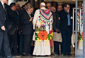 """21 octobre 2019 : Synode sur l'Amazonie. A son arrivée à la salle du synode, le pape François, accompagné de Mgr Lafont, reçoit en cadeau un châle et un paréo sur lequel est inscrit une parole tirée du Nouveau Testament """"soyez courageux, j'ai vaincu le monde""""."""